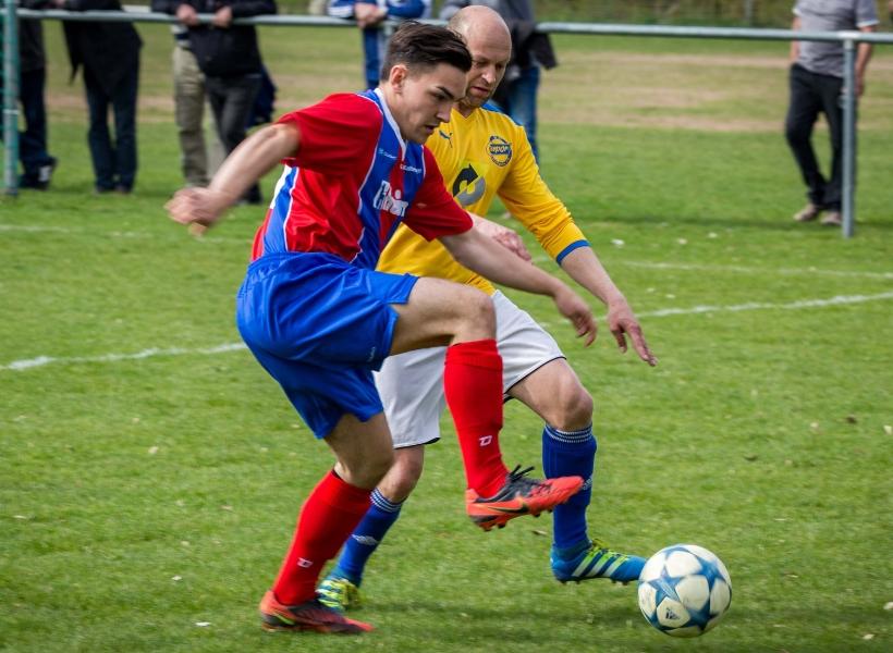 Zwei Männer in verschiedenfarbigen Trikots spielen Fußball