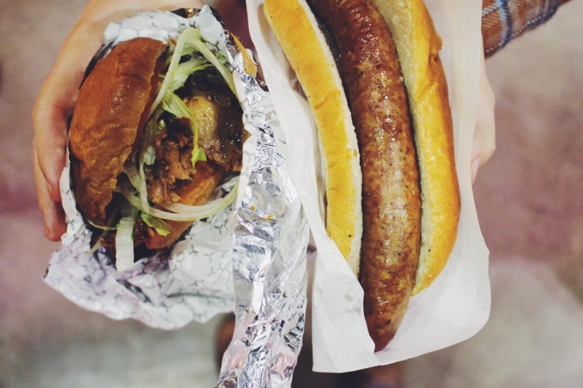 Eine Hand hält einen Burger und ein fettiges Wurstbrot