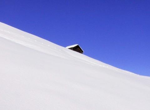 Eine einsame Hütte in Schneelandschaft, blauer Himmel