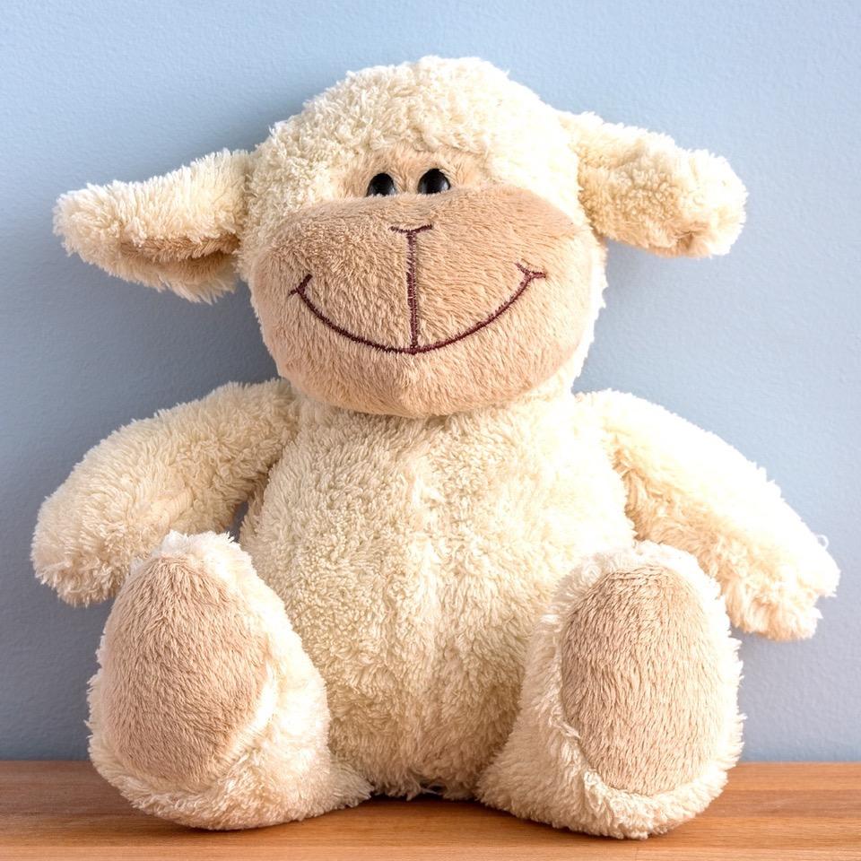 Ein lächelndes Stoff-Schaf sitzt an einer Wand