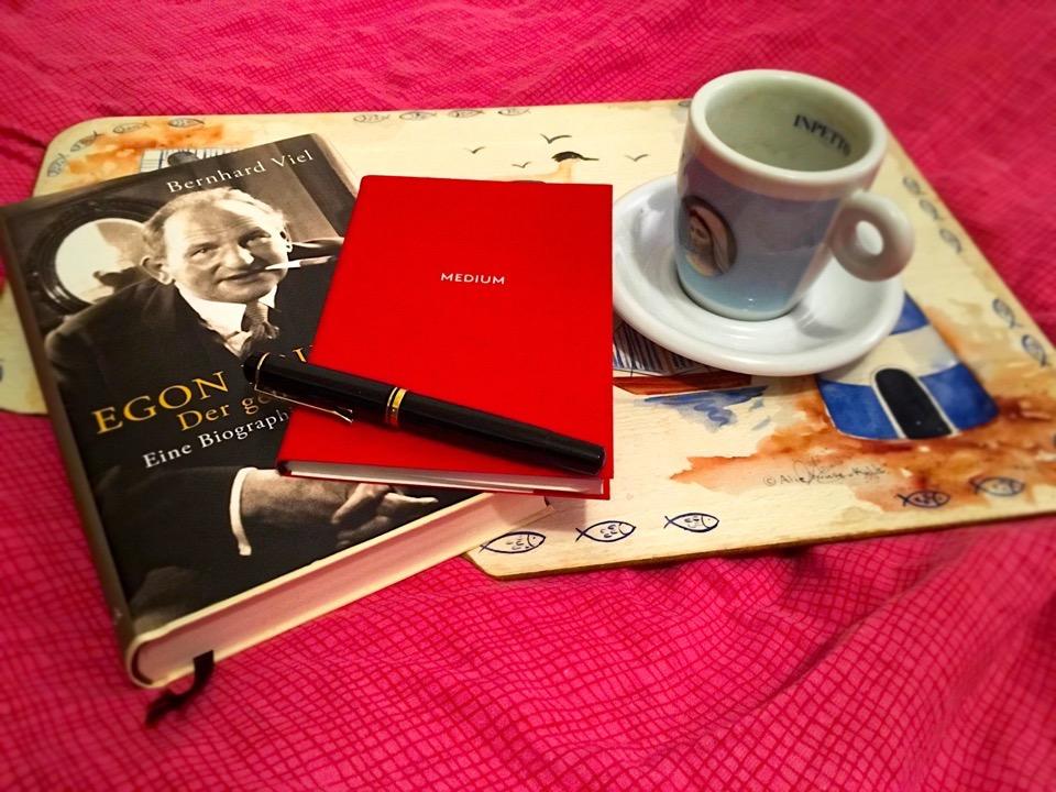 Ein Buch, ein rotes Notizbuch und eine Espressotasse auf einen Brett, das auf einer roten Bettdecke liegt