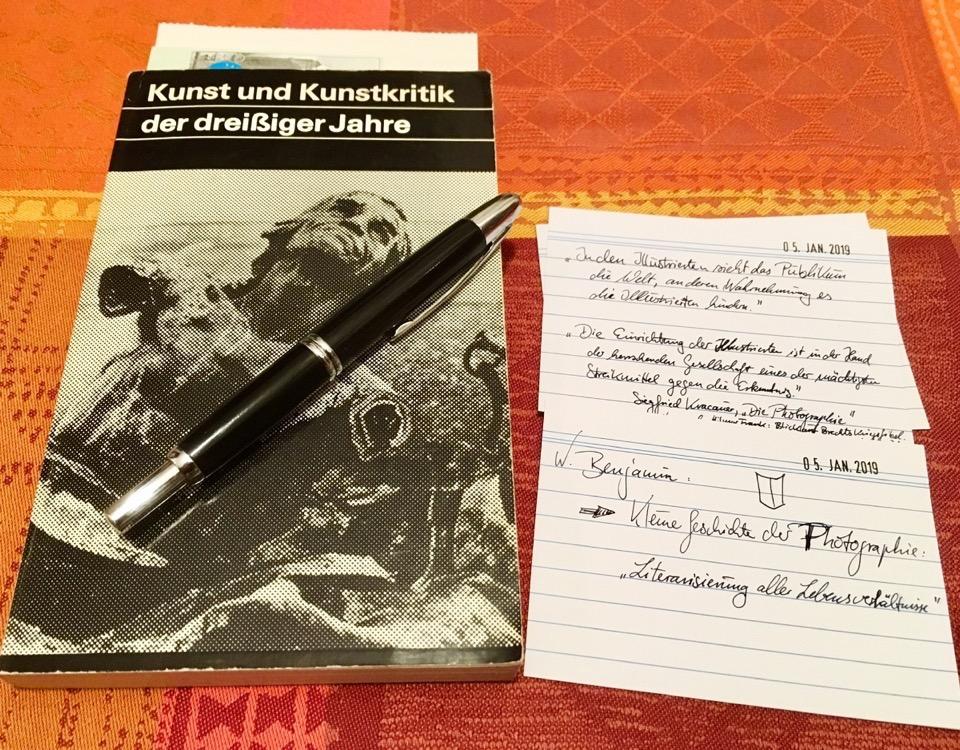 Ein Buch, ein Füller und zwei beschriebene Karteikarten liegen auf einem Tisch