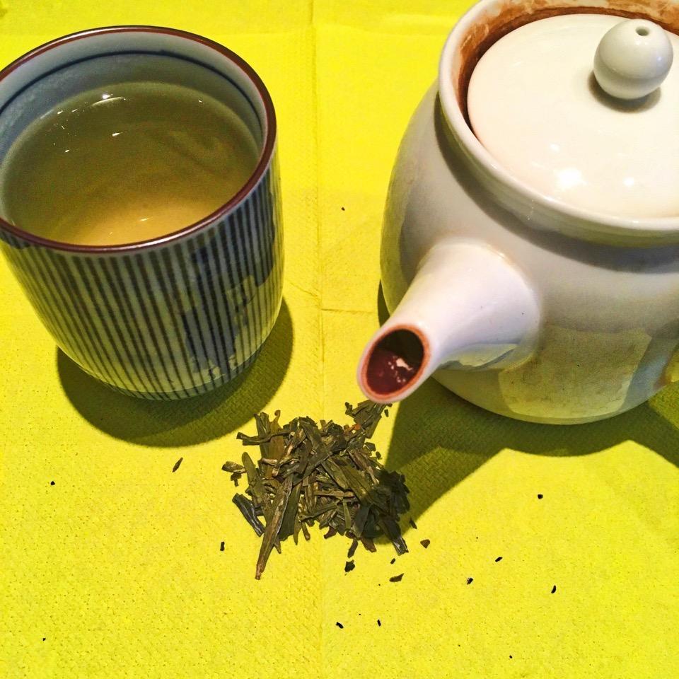 Eine Tasse, eine Kanne und Grüner Tee