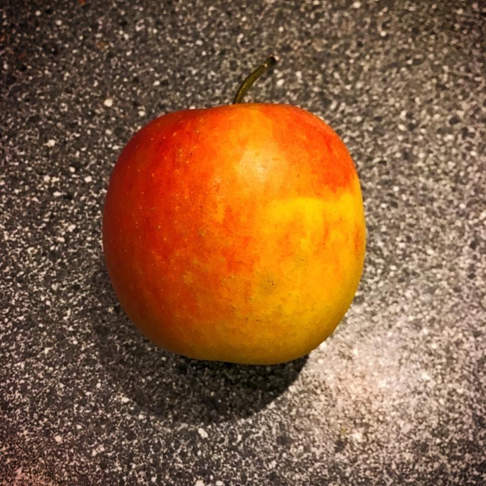 Ein rot-gelber Apfel auf einer Tischplatte