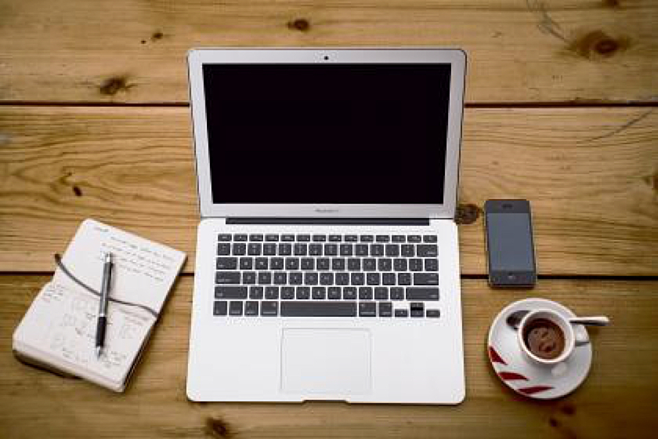 Ein Laptop, ein Mobiltelefon, ein Notizbuch und eine Tasse Kaffee auf einem Holztisch