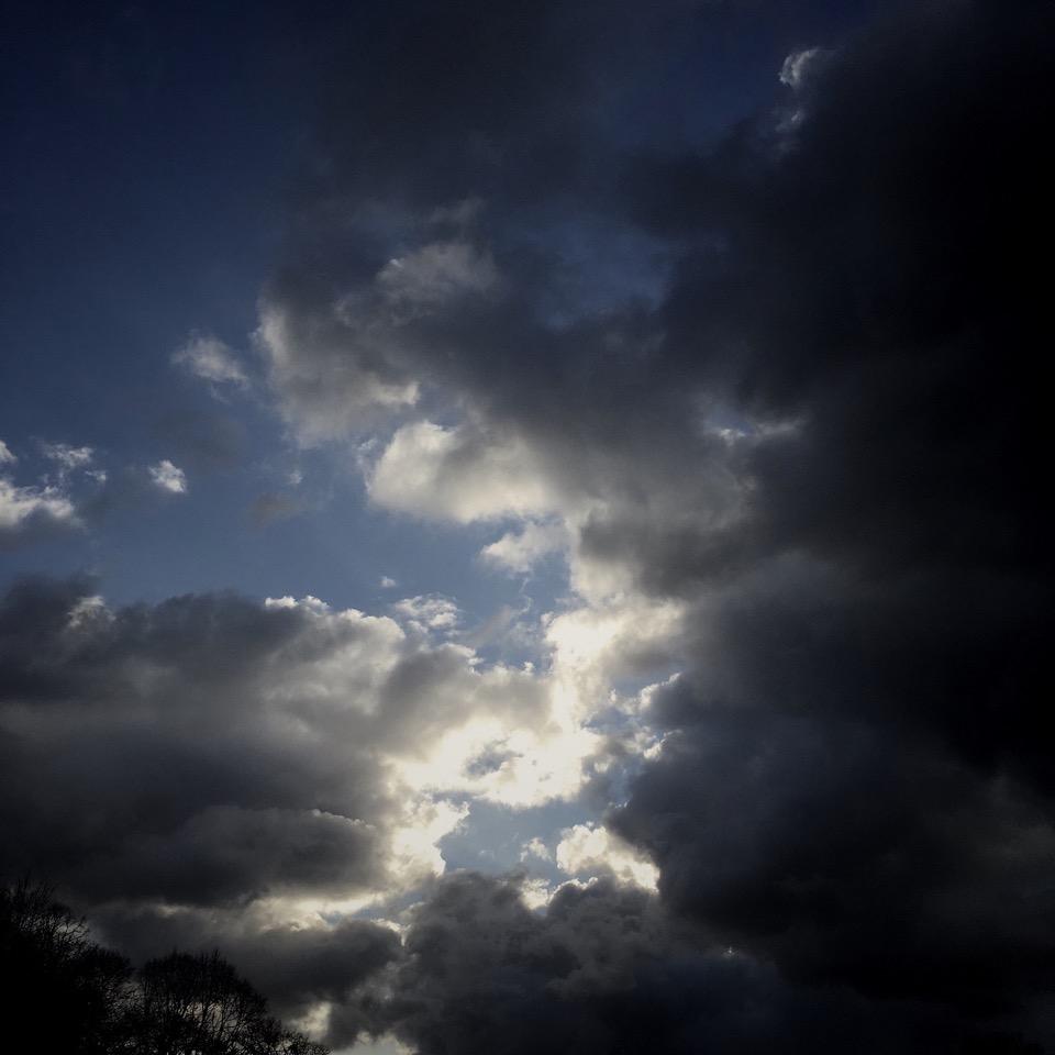 Himmel mit dunklen Wolken, durch die etwas Sonne dringt