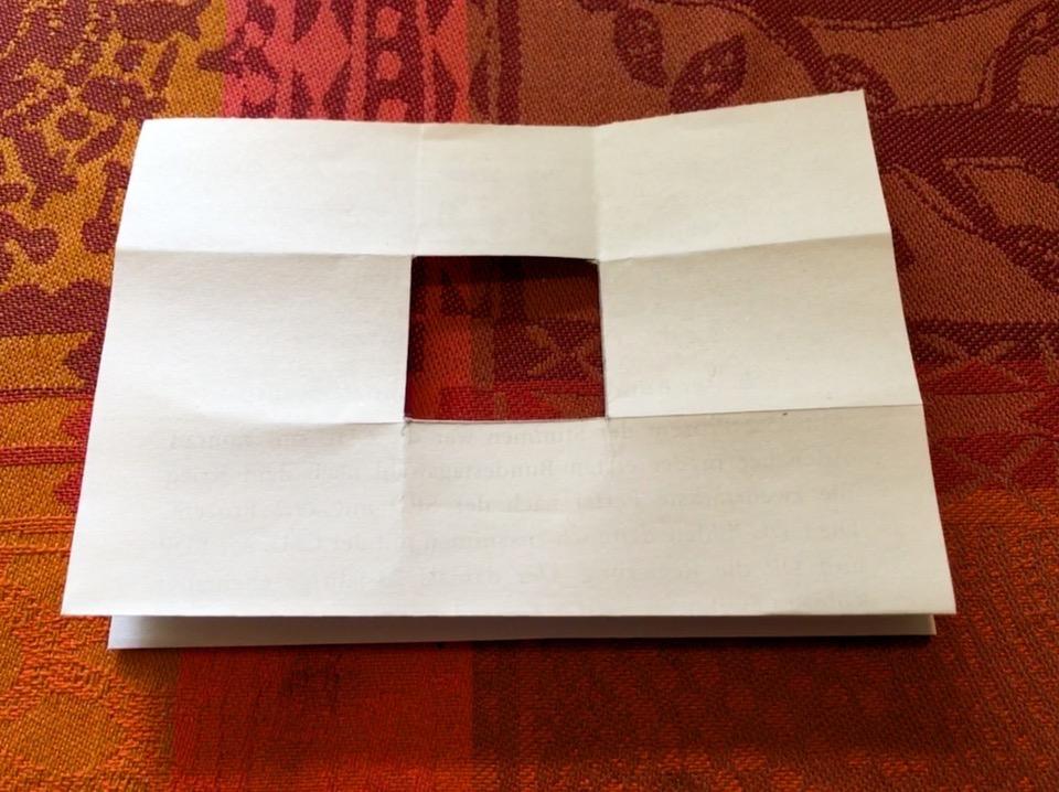Ein gefaltetes Blatt Papier, aus dem in der Mitte ein Quadrat ausgeschnitten wurde, liegt auf eine rot-orange gemusterten Tischdecke