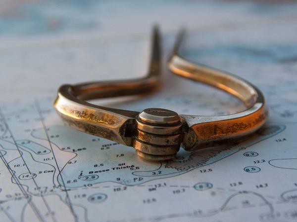 Ein antiker Zirkel liegt auf einer Seekarte